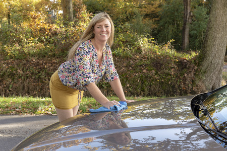 Woman wearing a floral top polishing her car 写真素材 - 112659226