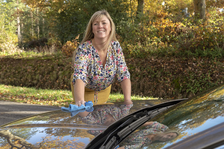 Woman wearing a floral top polishing her car