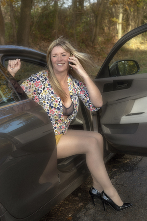 Attractive mid aged woman driver stepping out of a car using a mobile telephone