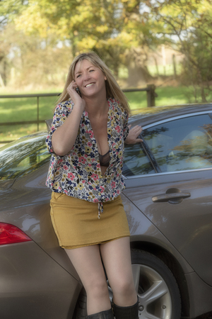 Attractive mid aged woman driver out of a car using a mobile telephone on a country road