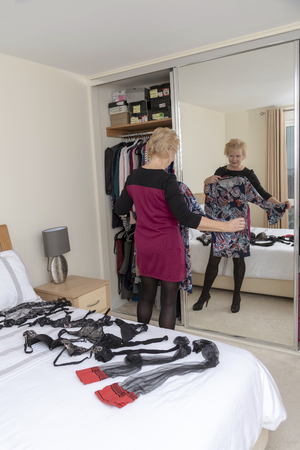 Woman selecting clothes from her wardrobe in a bedroom with full length mirror