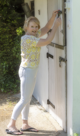 An elderly woman locking a stable door.