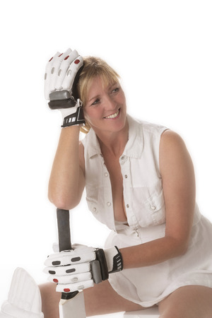 woman cricketer in a revealing dress seated with her gloved hand resting on her head