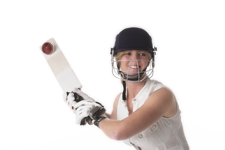Woman cricketer in a white dress with a safety helmet, shin pads, a bat and ball.