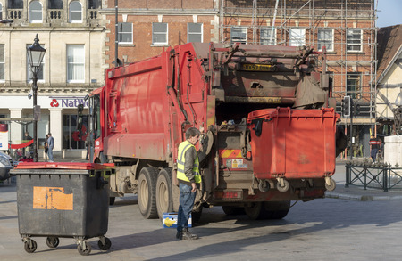 Salisbury, Wiltshire, England, UK. February 2019. Operative loading a commercial size red refuse bin into a truck in the city centre.