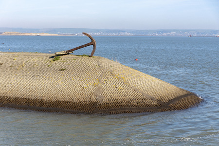 Appledore, North Devon, England, UK. February 2019. Man made breakwater with an old anchor on Appledore Harbour Redactioneel