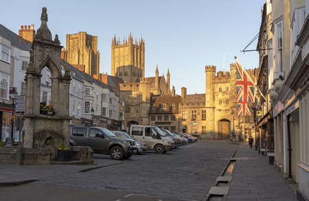 Wells, Somerset, England, UK. March 2019. Glowing sun illuminates the Market Place,and Bishops Eye Gatehouse and cathedral towers,  in the cathedral city in the Mendip district of Somerset.