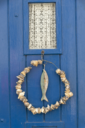 Appledore, North Devon, England, UK. March 2019. Door knocker of a fish carved from wood and shells on a wire decorate this cottage door. Editorial