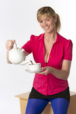 Southern England UK.  Attractive woman wearing a revealing red shirt pouring a cup of tea 版權商用圖片