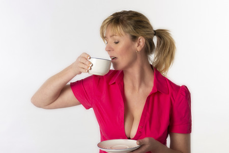 Southern England UK. Attractive woman wearing a revealing red shirt drinking a cup of tea