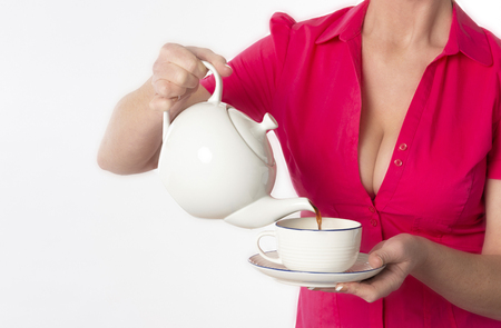 Southern England UK.  Attractive woman wearing a revealing red shirt pouring a cup of tea Stock Photo