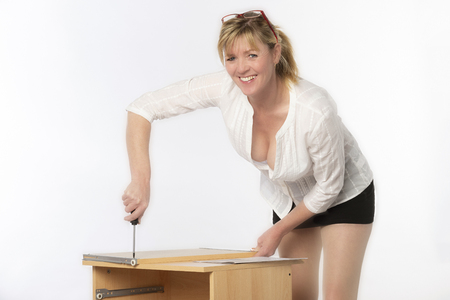 Woman constructing a personal computer desk from a flatpack, Using the instructions and a screwdriver