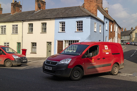 Devizes, Wiltshire, England, UK. March 2019. Red postal vans on Long Street in the town centre.
