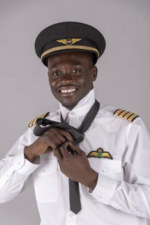 Portrait of an airline pilot tying his uniform black tie Stock Photo