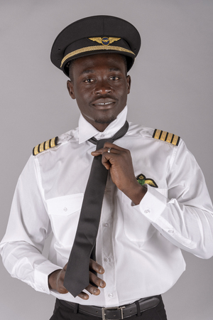 Retrato de un piloto de línea aérea atando su uniforme de corbata negra