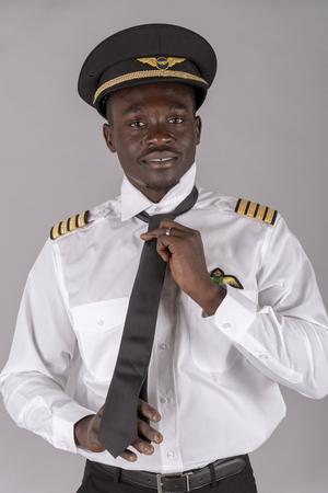Ritratto di un pilota di linea che si allaccia la cravatta nera dell'uniforme