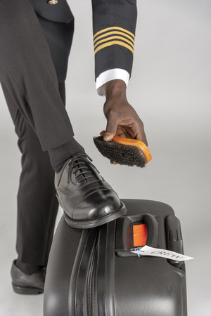 Airline pilot brushing his black uniform shoes.