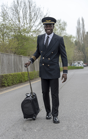 Airline pilot in uniform walking to work pulling a flight bag.