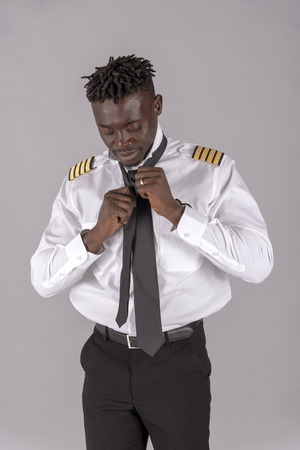 A young airline pilot with an african dred hairstyle. Crew member tying his black tie,