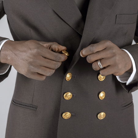 Lieutenant Commander wearing uniform of the South African Navy. Buttoning his uniform jacket.