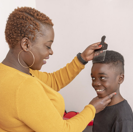 Nine year old boy with curly hair with his mother using a wide tooth afro comb for his hair.