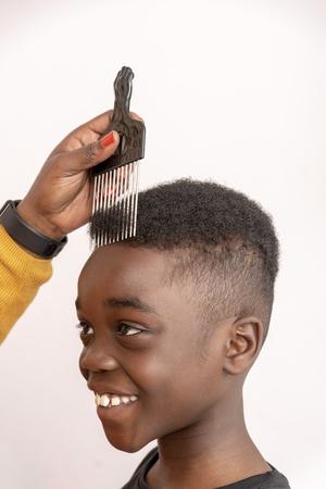 Garçon de neuf ans aux cheveux bouclés avec sa mère à l'aide d'un peigne afro à dents larges pour ses cheveux.