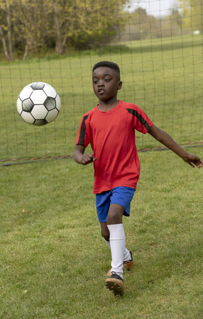 A young football player defending the goal during a traning session in a public park.
