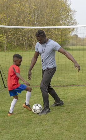 Young soccer player being coached on a football pitch. Stockfoto
