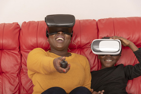 Mother and son wearing reality glasses sitting on a red leather sofa