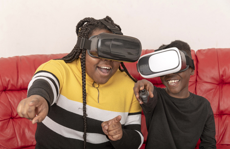 Young girl  and boy laughing wearing reality glasses sitting on a red leather sofa