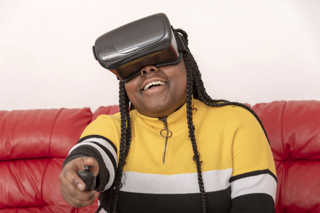 Young girl  laughing wearing reality glasses sitting on a red leather sofa Stock Photo