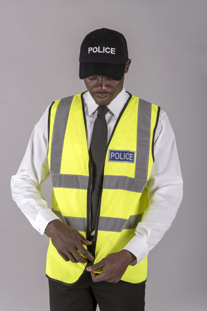 Portrait of a police officer zipping up his uniform jacket Stock Photo