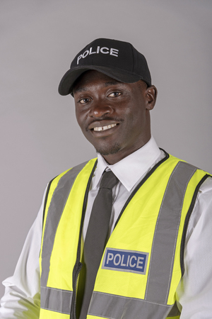Portrait of a smiling, police officer wearing a cap and reflective uniform jacket.