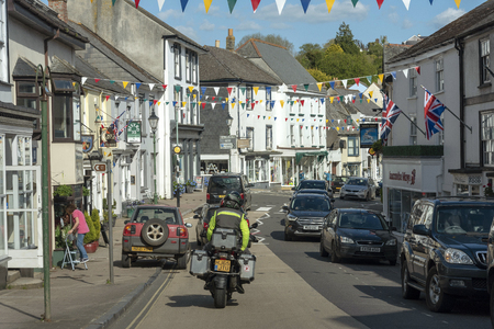 Modebury, South Devon, England, UK. May 2019. Rear view of a motorcyclist passing through this old Devonshire market town.