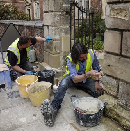 Salisbury, Wiltshire, England, UK. Stone masons working on a gateway, replacing stone and repairing mortar. 報道画像