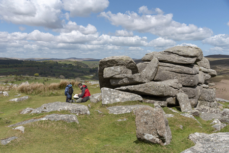 Dartmoor National Park, Devon, England, UK, May 2019. Man and boy consulting paperwork on the Combestone Tor high on Dartmoor.