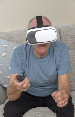 Elderly man having fun and frights wearing a pair of virtual reality goggles