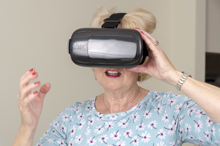 Elderly woman pull over her head a pair of virtual reality goggles