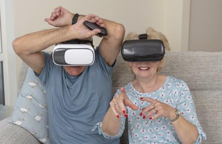 Elderly couple having fun wearing virtual reality goggles Stock Photo
