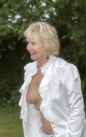 Senior woman removing a white shirt to reveal her breasts.