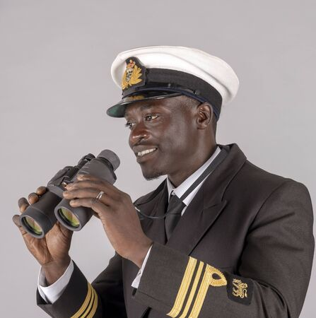 A naval officer in uniform holding a pair of binoculars