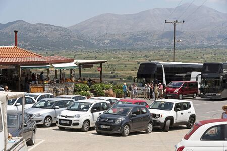 Lassithi, Crete, Greece. June 2019. Tour buses and visitors cars parked with a background of the Lassithi Plateau a fertile area for produce growing.