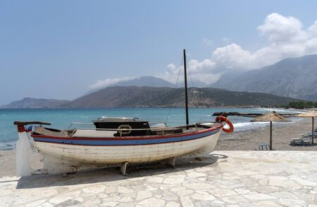Crete, Greece. June 2019. A small boat painted red white blue with a background of the coast and mountains
