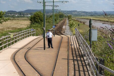 Seaton, Devon, England, UK. June 2019.  A tramway employee at the Riverside Depot stop alongside the River Axe in East Devon.