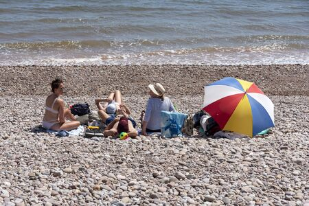 Sidmouth, Devon, England, UK. July 2019. Holidaymakers with a colourful umbrella on the shingle beach at Sidmouth eastern Devon.