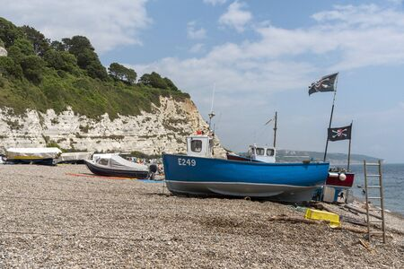 Beer near Seaton, Devon, England, UK. Beer beach on the Jurassic Coast in East Devon. Fishing boats and white calk cliffs.