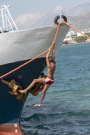 Ierapetra, Crete, Greece, June 2019. A small boy playing on the bow ropes of a ship. Ierapetra port, Crete.