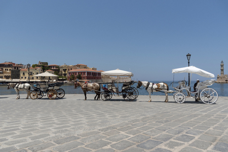 Chania, Crete, Greece, June 2019. Horse drawn carriages waiting on the Old Venetion Harbour in Chania to take passengers on a ride.