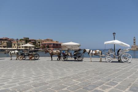 Chania, Kreta, Griechenland, Juni 2019. Pferdekutschen warten auf den alten Hafen von Venetion in Chania, um Passagiere auf eine Fahrt zu bringen.
