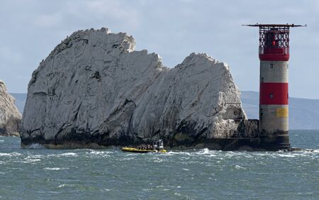 The Needles, Isle of Wight, England, UK. September 2019. The Needles lighthouse with helipad situated on the outermost chalk rocks. Passengers on a rib viewing the rocks and lighthouse. Isle of Wight, UK Editorial